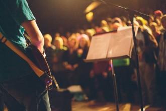 Man playing a guitar at a worship service